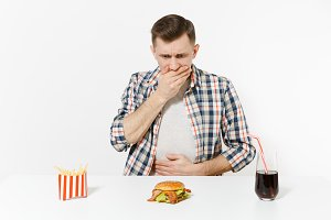 Illness man put hands on pain abdomen, stomach-ache at table with burger, french fries, cola in glass isolated on white background. Proper nutrition or American classic fast food. Area with copy space