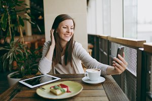 Smiling woman in coffee shop with cup of cappuccino, cake, doing selfie on mobile phone, relaxing in restaurant during free time. Female sitting with pc tablet computer rest in cafe. Lifestyle concept