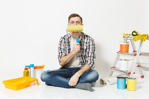 Fun man sitting on floor with paint roller like mustache, instruments for renovation apartment room isolated on white background. Wallpaper, gluing accessories, painting tools. Repair home concept.