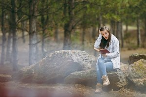 Young shocked beautiful woman sitting on stone studying reading book and clinging to head in city park or forest on green blurred background. Student learning, education. Lifestyle, leisure concept.
