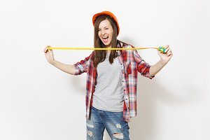 Young overjoyed woman in casual clothes, protective construction helmet holding toy measure tape isolated on white background. Instruments, tools for renovation apartment room. Repair home concept.
