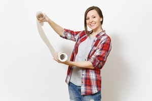 Young smiling beautiful woman in casual clothes holding unrolled wallpaper roll isolated on white background. Instruments, accessories, tools for renovation apartment room. Repair home concept.