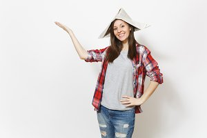 Young smiling beautiful woman in newspaper hat pointing hand aside on copy space isolated on white background. Accessories for renovation apartment room. Repair home concept. Advertising area.