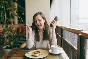 Young woman sitting in coffee shop at table with cup of cappuccino, cake, relax in restaurant during free time. Young female listen music in earphones on mobile phone, rest in cafe. Lifestyle concept.