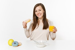 Young woman sitting at table breakfast with cereals and milk, orange juice in glass, donuts isolated on white background. Proper nutrition, delicious tasty food, healthy lifestyle. Area to copy space.