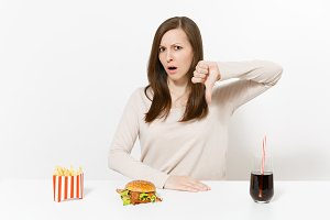Irritated woman shows thumbs down at table with burger french fries cola in glass bottle isolated on white background. Proper nutrition or American classic fast food. Advertising area with copy space.