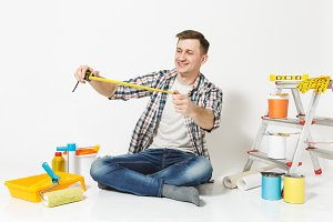 Man in casual clothes sitting on floor with measure tape, instruments for renovation apartment room isolated on white background. Wallpaper, gluing accessories, painting tools. Repair home concept.