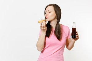 Beautiful fun brunette woman holding in hands colorful donuts, cola in glass bottle isolated on white background. Proper nutrition or sweets, dessert, fast food concept. Advertising area to copy space