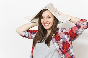 Portrait of young smiling beautiful woman in newspaper hat clinging to head isolated on white background. Accessories for renovation apartment room. Repair home concept. Copy space for advertisement.