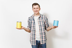 Young smiling man in casual clothes holding empty paint tin cans with copy space isolated on white background. Instruments, accessories, tools for renovation apartment room. Repair home concept.