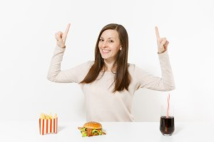 Young woman pointing fingers up on copy space at table with burger, french fries, cola in glass bottle isolated on white background. Proper nutrition or American classic fast food. Advertising area.