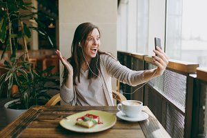 Young woman sitting alone in coffee shop at table with cup of cappuccino, cake, relaxing in restaurant during free time. Young female doing selfie on mobile phone, rest in cafe. Lifestyle concept.