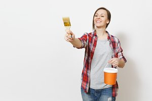 Young smiling beautiful woman holding paint bucket, pointing paint brush on copy space isolated on white background. Instruments, accessories, tools for renovation apartment room. Repair home concept.