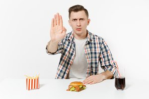 Severe man showing stop gesture with palm, sitting at table with burger, french fries, cola in glass isolated on white background. Proper nutrition or American classic fast food. Area with copy space.