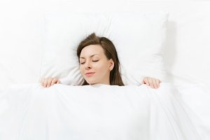 Top view of head of happy brunette young woman lying in bed with white sheet, pillow, blanket. Sleeping pretty female spending time in room. Rest, relax good mood concept. Copy space for advertisement