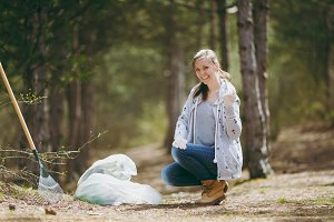 Young smiling woman cleaning rubbish into trash bags and showing fist in park or forest on green background. Problem of environmental pollution. Stop nature garbage, environment protection concept.