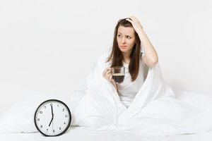 Tired sad woman sitting in bed with cup of coffee, round clock, white sheet, pillow, wrapping in blanket on white background. Female wake up early in morning, time in room. Rest, good mood concept.