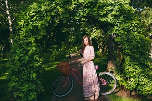 Portrait of trendy young woman in long pink floral dress stop to riding under oak arch on bike with basket for purchases, food or flowers outdoors, cute female recreation time in spring or summer park