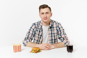 Handsome young man in shirt sitting at table with burger, french fries, cola in glass isolated on white background. Proper nutrition or American classic fast food. Advertising area with copy space.