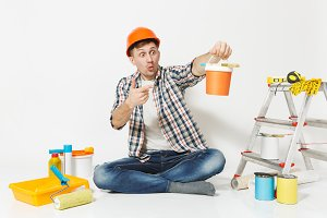 Shocked man in orange protective helmet sitting on floor with paint can, instruments for renovation apartment isolated on white background. Wallpaper, accessories, painting tools. Repair home concept.