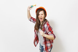 Young irritated dissatisfied woman in protective construction helmet swinging toy hammer and screaming isolated on white background. Instruments for renovation apartment room. Repair home concept.