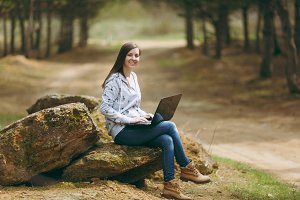 Young smiling successful smart business woman or student in casual clothes sitting on stone using laptop in city park or forest working outdoors on green blurred background. Mobile Office concept.