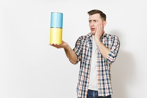 Young shocked handsome man holding empty paint tin cans with copy space and keeping hands near face isolated on white background. Instruments for renovation apartment room. Repair home concept.