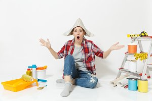 Shocked woman in newspaper hat spreading hands, sitting on floor with instruments for renovation apartment isolated on white background. Wallpaper, accessories, painting tools. Repair home concept.
