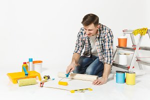 Young man sitting on floor with wallpaper roll, paint roller, instruments for renovation apartment room isolated on white background. Wallpaper, gluing accessories, painting tools. Repair home concept