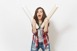 Irritated woman in casual clothes holding wallpaper rolls and screaming isolated on white background. Instruments, accessories for renovation apartment room. Repair home concept. Advertising area.