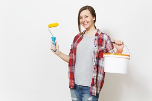 Smiling woman holding paint roller for wall painting and empty bucket with copy space isolated on white background. Instruments, accessories, tools for renovation apartment room. Repair home concept.