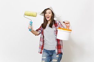 Overjoyed woman in newspaper hat holding paint roller for wall painting and empty paint bucket with copy space isolated on white background. Instruments for renovation apartment. Repair home concept.