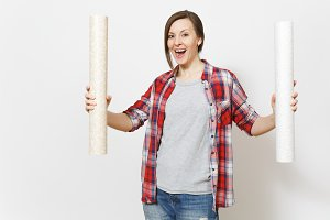 Young overjoyed beautiful woman in casual clothes holding wallpaper rolls isolated on white background. Instruments, accessories for renovation apartment room. Repair home concept. Advertising area.