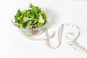 Close up green vegetables salad in glass bowl, tailor measuring tape isolated on white background. Proper nutrition, vegetarian food, healthy lifestyle, diet meal. Diabetes dieting concept. Copy space