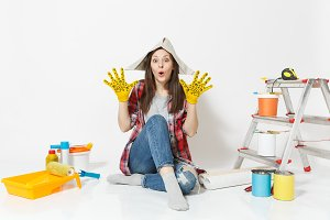 Pretty woman in newspaper hat, yellow gloves sitting on floor with instruments for renovation apartment isolated on white background. Wallpaper, gluing accessories, painting tools. Repair home concept