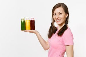 Fun woman holds row of green, red, yellow detox smoothies in bottles isolated on white background. Proper nutrition, vegetarian drink, healthy lifestyle, dieting concept. Copy space for advertisement.