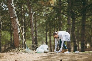 Young woman in casual clothes, gloves cleaning rubbish into trash bags in park or forest on green background. Problem of environmental pollution. Stop nature garbage, environment protection concept.