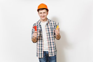 Young smiling handsome man in protective orange hardhat holding toy screwdriver and adjustable wrench isolated on white background. Instruments for renovation apartment room. Repair home concept.