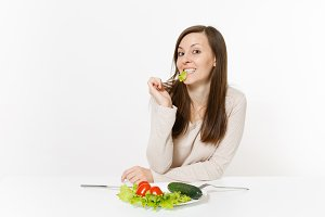 Vegan woman at table with leaves salad lettuce, vegetables on plate isolated on white background. Proper nutrition, vegetarian food, healthy lifestyle dieting concept. Advertising area with copy space