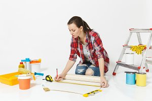 Woman sitting on floor with wallpaper rolls, measure tape, instruments for renovation apartment isolated on white background. Accessories for gluing, painting tools. Repair home concept. Copy space.