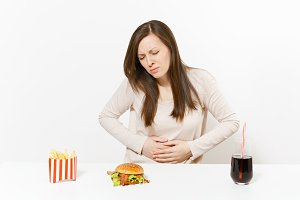 Illness woman put hands on pain abdomen, stomach-ache at table with burger, french fries, cola in glass bottle isolated on white background. Proper nutrition or American classic fast food. Copy space.