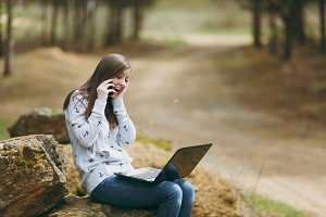 Young laughing business woman or student in casual clothes sitting on stone talking on mobile phone in city park or forest using laptop working outdoors on green background. Mobile Office concept.
