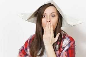 Portrait of young irritated beautiful woman in newspaper hat keeping hands near face isolated on white background. Accessories for renovation apartment room. Repair home concept. Advertising area.