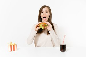 Beautiful young woman sitting at table with burger, french fries, cola in glass bottle isolated on white background. Proper nutrition or American classic fast food. Advertising area with copy space.