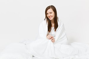 Young brunette woman sitting in bed with white sheet, pillow, wrapping in blanket on white background. Beauty female spending time in room. Rest, relax, good mood concept. Copy space for advertisement