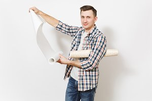 Young handsome man in casual clothes holding unrolled wallpaper roll isolated on white background. Instruments, accessories, tools for renovation apartment room. Repair home concept. Advertising area.