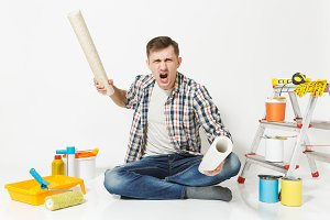 Screaming aggressive angry young man with rolls of wallpaper, sitting on floor with instruments for renovation apartment isolated on white background. Gluing accessories, tools. Repair home concept.
