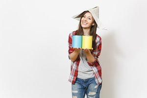 Young smiling beautiful woman in casual clothes and newspaper hat holding paint tin cans isolated on white background. Instruments, accessories for renovation apartment room. Repair home concept.