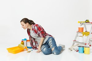 Woman in casual clothes look aside, sit on floor with instruments for renovation apartment room isolated on white background. Wallpaper, accessories for gluing, painting tools. Concept of repair home.