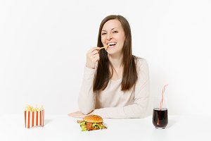 Fun happy woman at table with several pieces of potatoes, french fries, burger, cola in glass bottle isolated on white background. Proper nutrition or American classic fast food. Area with copy space.